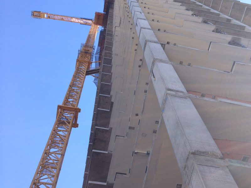 A view of a tall building from the ground with a crane on the left