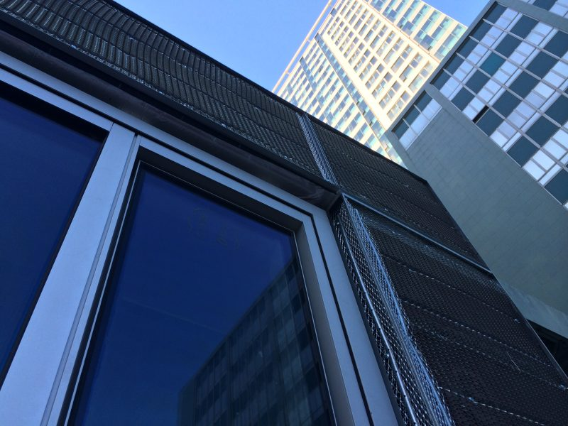 A view of a building's window with a taller building behind