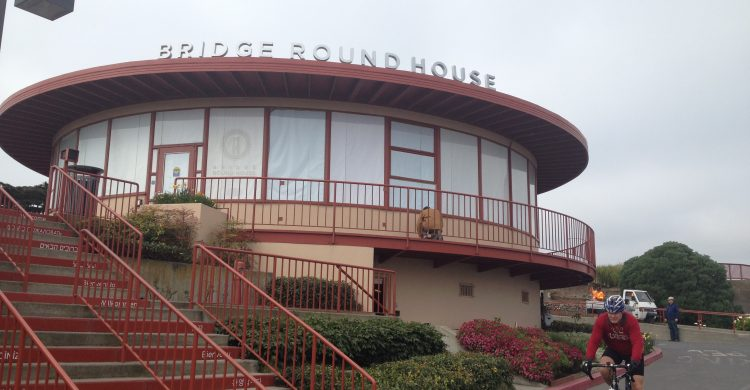 """A round red and tan building labeled """"Bridge Roundhouse"""""""